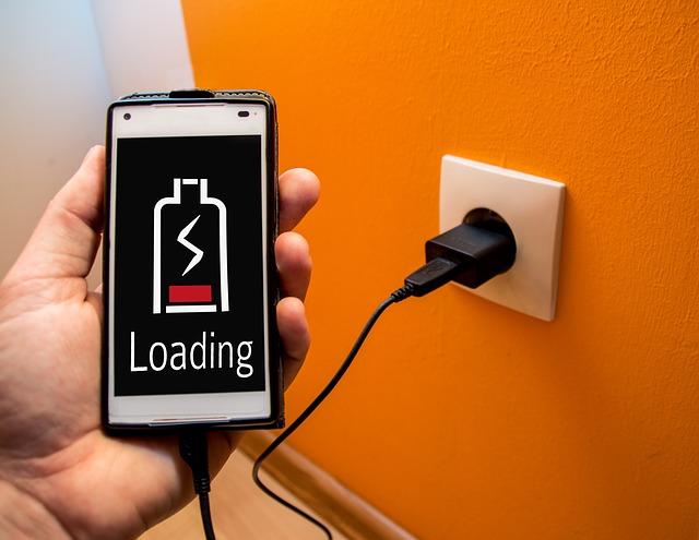 bílá zásuvka na oranžové stěně, nabíjení telefonu.jpg